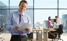 Smiling businessman holding paperwork with co-workers working in background