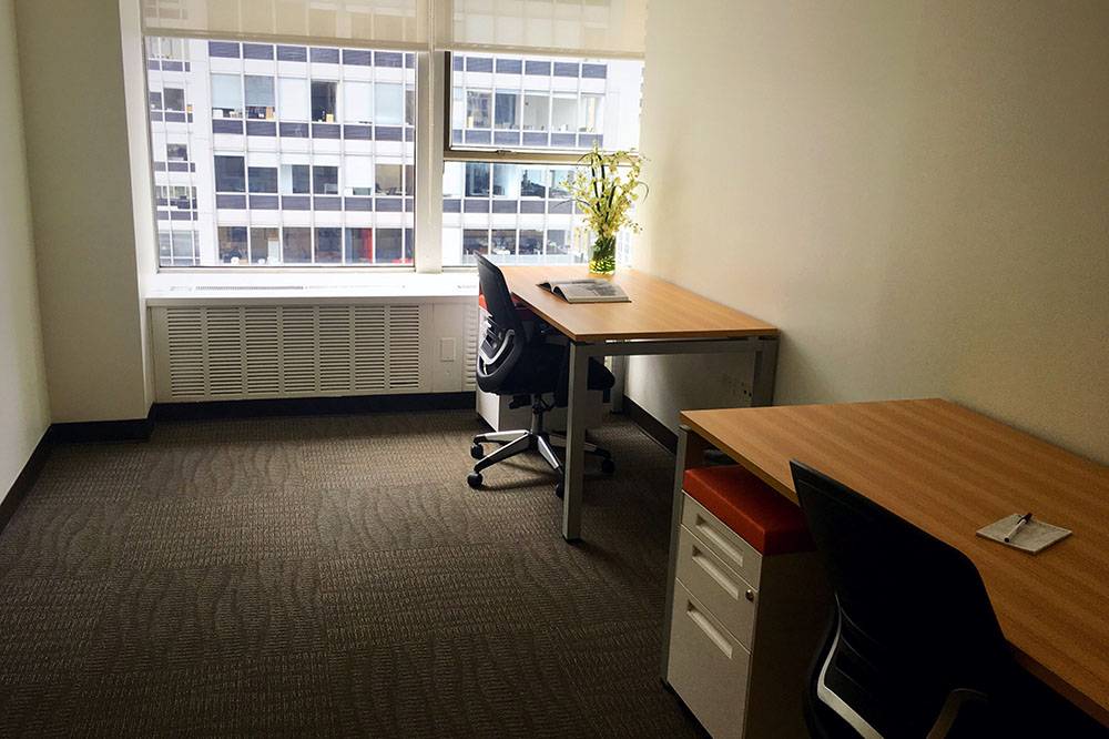two desks and a window view